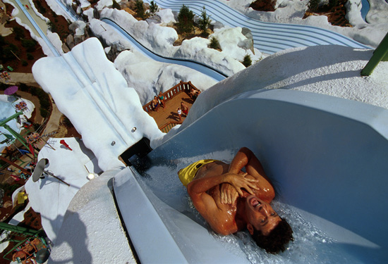 "Today in Disney history is a milestone for Disney's Blizzard Beach Water Park, which opened its doors on April 1, 1995. In honor of the anniversary, here are 10 fun facts about this place.  Summit Plummet, the park's signature attraction, measures 120 feet tall. The park's storyline described the park as being Florida's first ski resort – which quickly melted into a fun water park due to the temperature. One of the ""ski resort"" elements that still remains is a chair lift, which takes guests from the beach to the top of Mt. Gushmore.  The park debuted an original character, Ice Gator, as part of it's storyline. When it comes to speed, guests can slide up to 55 mph on Summit Plummet and 25 mph on the Downhill Double Dipper. Teamboat Springs is the world's longest family raft ride. Up to six can ride per raft.  Tike's Peak, an area for young children, features a scaled-down version of Mt. Gushmore. Teamboat Springs features a 1,200-foot series of rushing waterfalls.  One of the park's more unusual snacks are mini donuts, which are prepared fresh and offered up with chocolate, white chocolate or raspberry dipping sauce. In 2012, the park joined 500 host locations to help set the Guinness World Record for the World's Largest Swimming Lesson."